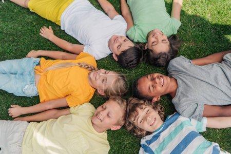 Photo pour Vue aérienne des enfants multiculturels heureux avec les yeux fermés couchés sur l'herbe - image libre de droit