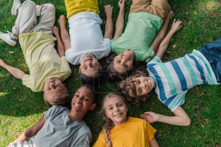 top view of happy multicultural kids lying on grass