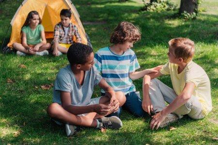 Photo pour Foyer sélectif des garçons multiculturels assis sur l'herbe - image libre de droit