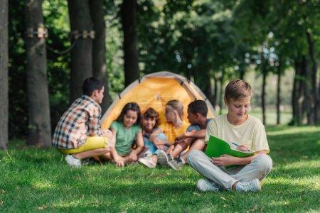 Foto de Enfoque selectivo de chico alegre escribir en cuaderno cerca de amigos multiculturales en el campamento - Imagen libre de derechos