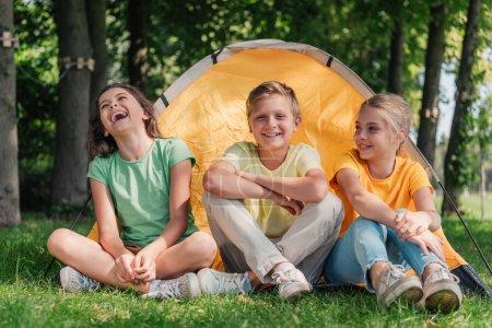 Photo pour Garçon heureux assis avec des amis mignons riant près du camp - image libre de droit
