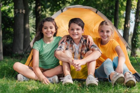 Photo for Happy boy sitting with cute friends near camp - Royalty Free Image