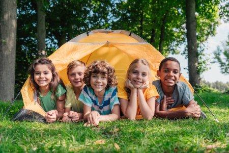 Foto de Niños alegres multiculturales sonriendo mientras están acostados cerca del campamento - Imagen libre de derechos