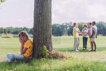 Photo pour Foyer sélectif de l'enfant assis près du tronc d'arbre près des enfants multiculturels - image libre de droit