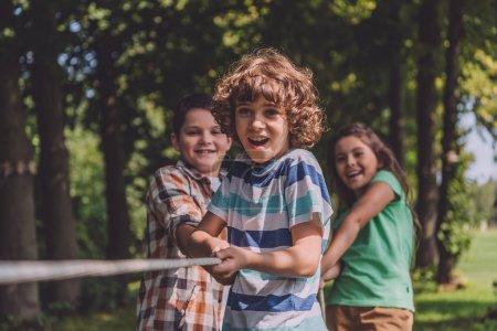 Foto de Enfoque selectivo de los niños alegres que compiten en tira y abarana de la guerra - Imagen libre de derechos