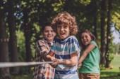 """Постер, картина, фотообои """"селективное внимание веселых детей, конкурирующих в перетягивание каната"""""""