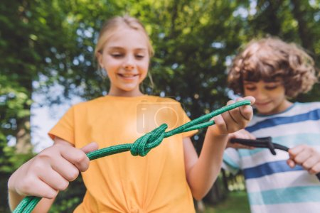 Foto de Selective focus of happy kids holding ropes in park - Imagen libre de derechos