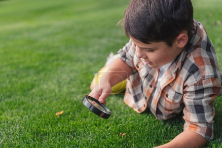 Photo for Selective focus of boy looking at grass through magnifier - Royalty Free Image
