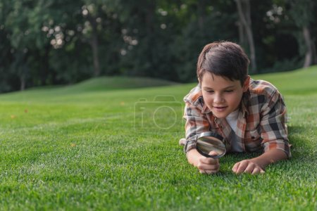 Photo pour Foyer sélectif de garçon mignon regardant l'herbe par loupe - image libre de droit