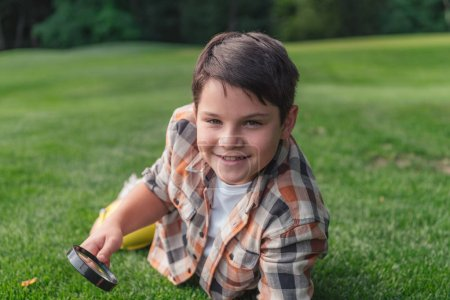 Foto de Enfoque selectivo de niño feliz sosteniendo la lupa mientras está acostado en la hierba - Imagen libre de derechos