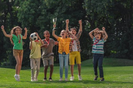 Photo for Happy multicultural kids football and trophy in park - Royalty Free Image