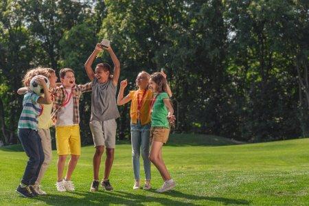 Foto de Niños multiculturales felices saltando sobre la hierba con el fútbol y el trofeo - Imagen libre de derechos