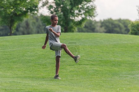 Photo for Cute african american boy exercising on grass - Royalty Free Image