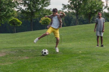 Foto de Lindo niño afroamericano de pie en la hierba cerca de amigo jugando al fútbol - Imagen libre de derechos