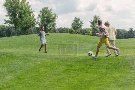 Foto de Lindo niño afroamericano mirando a los amigos mientras jugaba al fútbol - Imagen libre de derechos