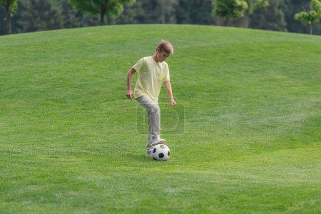 Photo pour Garçon mignon jouant au football sur l'herbe verte - image libre de droit