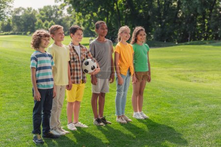 Photo for Happy multicultural kids standing on grass with football - Royalty Free Image