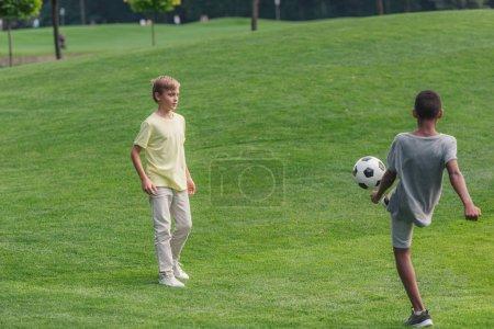 Photo pour Mignon enfants multiculturels jouer au football sur l'herbe - image libre de droit