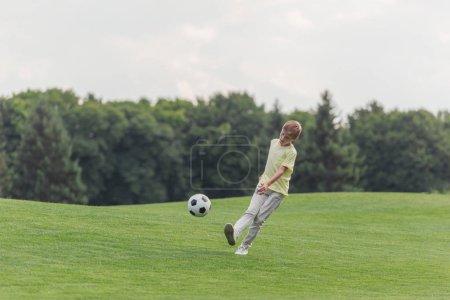 Foto de Chico lindo jugando al fútbol en hierba verde en el parque - Imagen libre de derechos