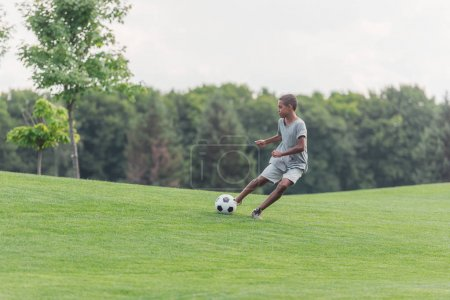 Photo for Cute african american boy playing football on green grass - Royalty Free Image