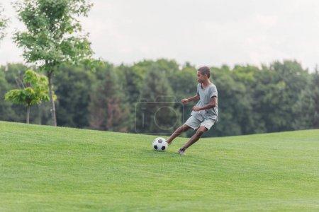Photo pour Garçon américain africain mignon jouant au football sur l'herbe verte - image libre de droit