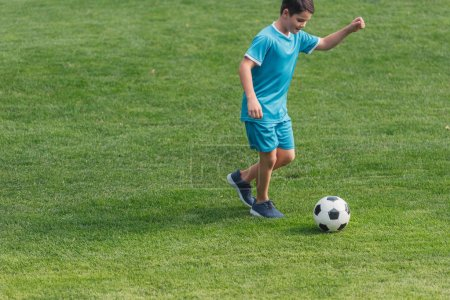 Photo pour Garçon mignon dans des vêtements de sport jouant au football sur l'herbe verte - image libre de droit