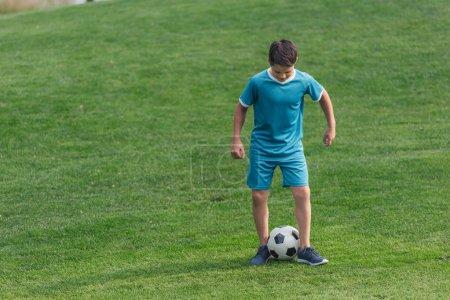 Foto de Niño en ropa deportiva de pie en la hierba verde con el fútbol - Imagen libre de derechos