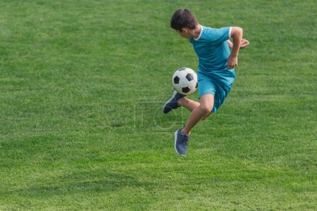 Photo for Kid in sportswear jumping on green grass with football - Royalty Free Image
