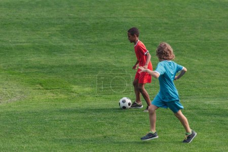 Photo for Cute multicultural kids playing football on grass - Royalty Free Image