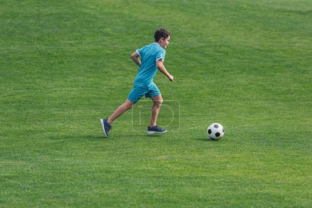 Photo for Kid in sportswear running on green grass with football - Royalty Free Image