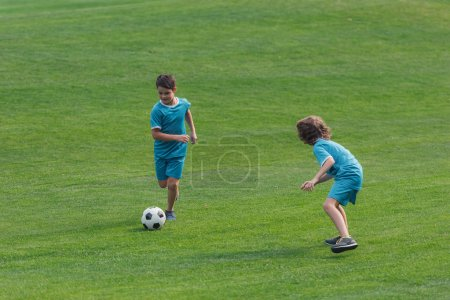 Foto de Cute boys in sportswear playing football on grass - Imagen libre de derechos