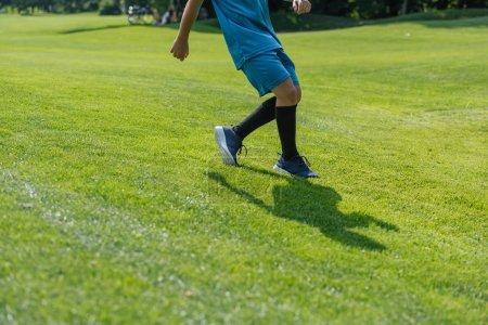 Photo pour Vue recadrée d'enfant fonctionnant sur l'herbe verte - image libre de droit