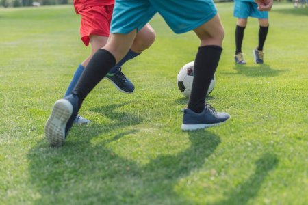 Foto de Cropped view of boys playing football on grass - Imagen libre de derechos