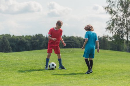 Foto de Cute curly boy playing football with friend on grass - Imagen libre de derechos