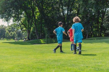 Photo pour Vue arrière du garçon bouclé jouant au football avec des amis sur l'herbe - image libre de droit
