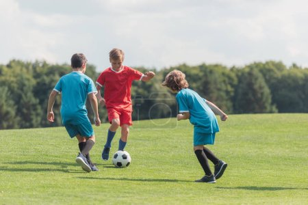 Photo for Curly boy playing football with friends on green grass - Royalty Free Image