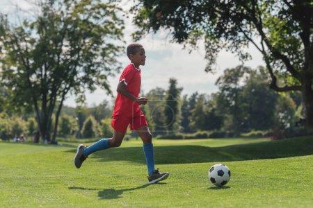 Photo pour Enfant américain africain mignon jouant au football sur l'herbe - image libre de droit