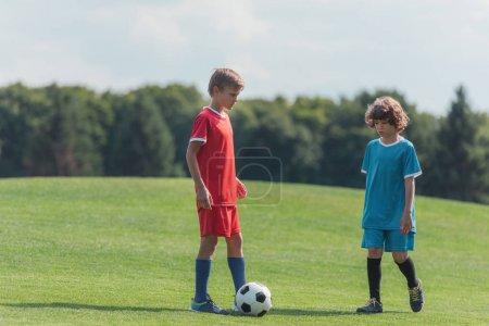 Foto de Lindo niño rizado jugando al fútbol con un amigo en la hierba en el parque - Imagen libre de derechos