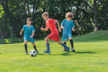 Photo pour Amis mignons dans des vêtements de sport jouant au football sur l'herbe verte dans le stationnement - image libre de droit
