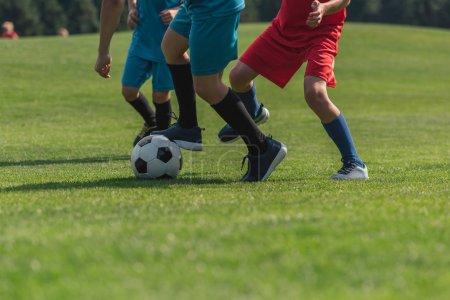 Foto de Vista recortada de tres niños jugando al fútbol en la hierba - Imagen libre de derechos