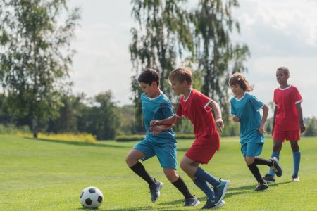 Photo for Four multicultural kids playing football on grass - Royalty Free Image