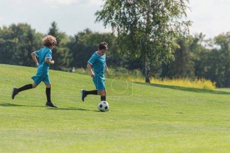 Photo pour Amis dans les sportswear bleus jouant au football sur l'herbe verte - image libre de droit