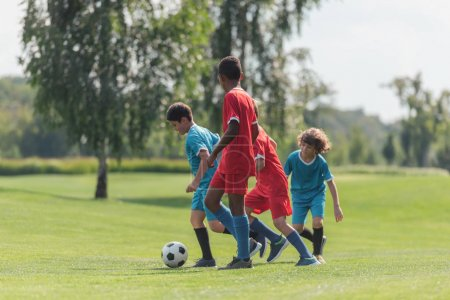 Photo pour Mignons enfants jouer au football avec un ami afro-américain - image libre de droit