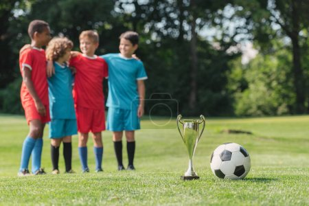 Photo for Selective focus of trophy and football near cute multicultural winners hugging outside - Royalty Free Image