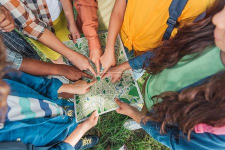 Photo for Overhead view of multicultural kids pointing with fingers at map outside - Royalty Free Image