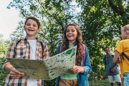 Photo pour Foyer sélectif des enfants heureux tenant carte près d'amis multiculturels - image libre de droit