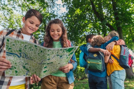 Photo for Selective focus of happy kids looking at map near multicultural friends hugging in park - Royalty Free Image
