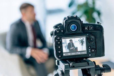 Photo pour Foyer sélectif de l'homme d'affaires de tir d'appareil-photo numérique dans le bureau - image libre de droit