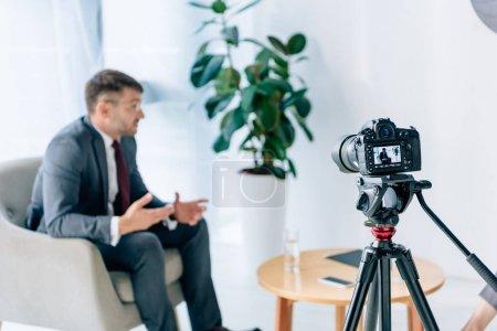 selective focus of digital camera shooting businessman in office