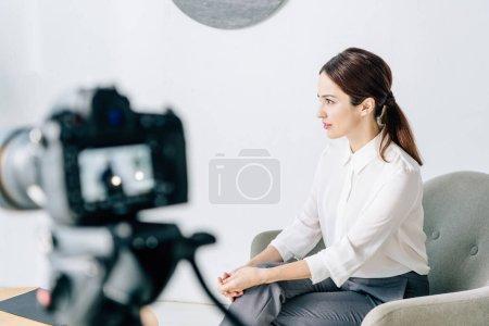 Photo pour Focus sélectif du journaliste en tenue de cérémonie assis dans un fauteuil - image libre de droit